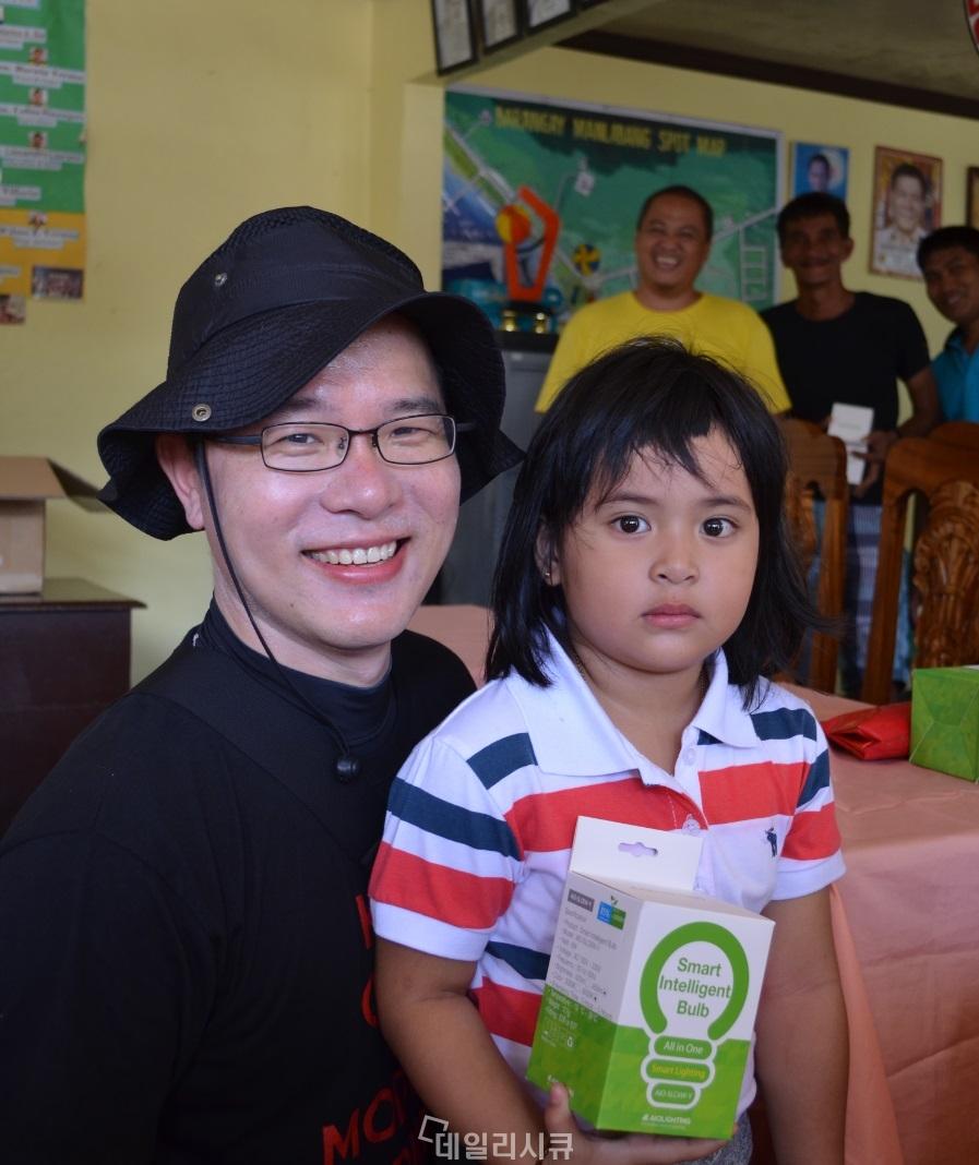 ▲ 모두스원 직원이 이 지역 어린아이에게 아인스링크의 스마트 이머전시 라이트를 전달하고 있다.