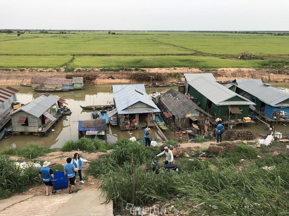 ▲ 캄보디아 시엠립 수상가옥이 밀집된 지역에 태양광 전구시설을 설치하기 위해 준비하고 있는 NSHC 직원들.